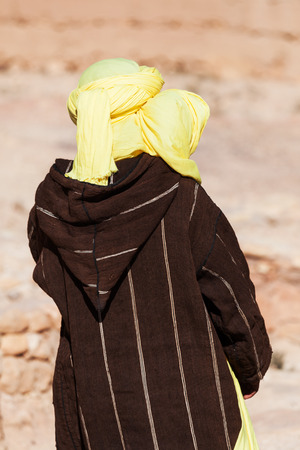 clothed: traditional clothed Tuareg from backside
