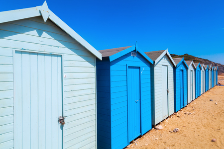 vanish: row of blue and white cabanas at the beach of Charmouth, Dorset, England