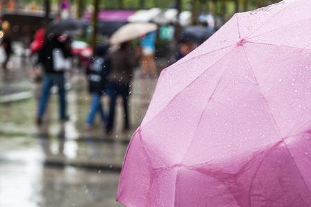 lluvia paraguas: paraguas de la lluvia con la gente borrosa en el fondo Foto de archivo
