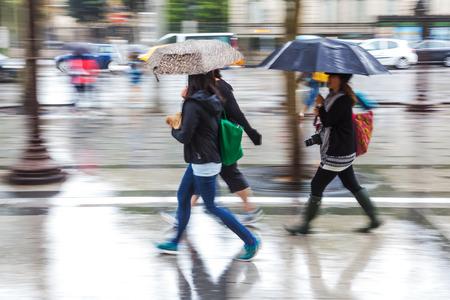 women with umbrellas walking in the rain rainy city in motion blur
