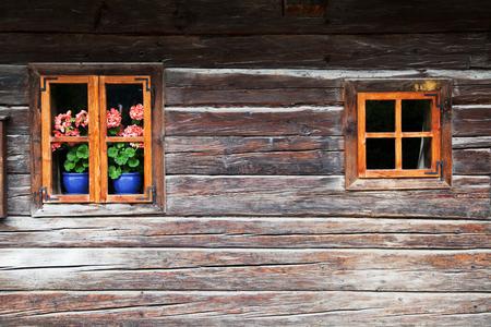 Detailansicht von zwei Fenstern auf einem sehr alten und malerischen Blockhaus in den österreichischen Alpen