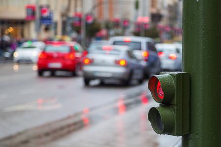 semaforo peatonal: sem�foros peatonales con tr�fico de la ciudad borrosa en una calle de lluvias en el fondo