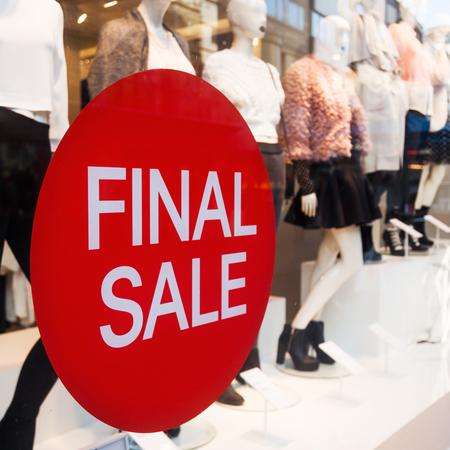 embleem met de uiteindelijke verkoop van letters voorzien bij een etalage van een kledingwinkel