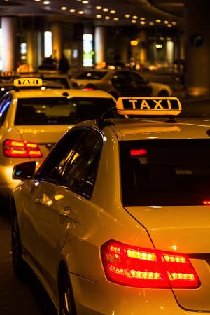 row of taxis at an airport at night