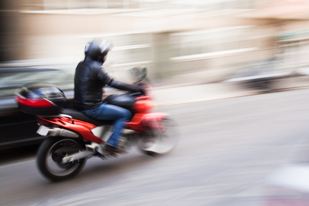 motorcycle rider in the city traffic in motion blur Archivio Fotografico