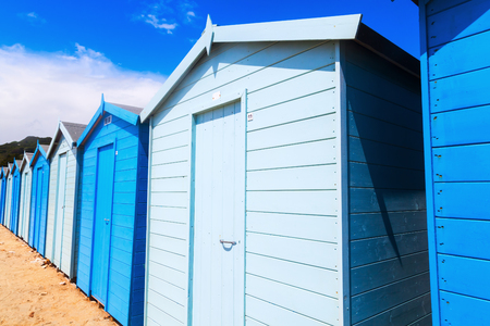 row of blue and white cabanas at the beach of Charmouth, Dorset, England