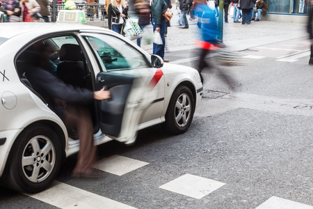 getting out: unrecognizable person getting out of a taxi in the city of Madrid Stock Photo