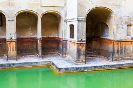 historical reflections: Bath, England - July 04, 2015: inside of Roman Baths with unidentified people, All All which is a site of historical interest in the city of Bath. The house is a well-preserved Roman site for public bathing