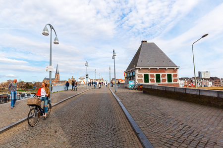 limburg: Maastricht, Netherlands - April 11, 2016: bridge over the river Meuse in Maastricht, with unidentified people. Maastricht is a university city and the capital of the Dutch province Limburg