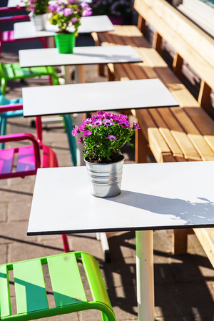 decoracion mesas: tables and chairs of a sidewalk cafe with flower decoration Foto de archivo