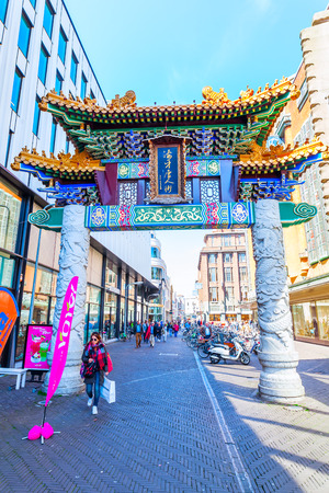 enclave: The Hague, Netherlands - April 21, 2016: Chinese Gate at the Chinatown in The Hague with unidentified people. A chinatown is an ethnic enclave of Chinese people and exists throughout the world Editorial
