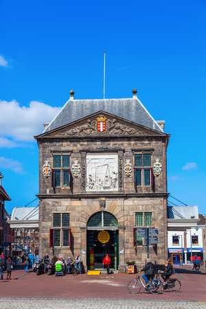 levy: Gouda, Netherlands - April 20, 2016: The Waag with unidentified people. It was built in 1667 and was used for weighing goods, especially cheese, to levy taxes. It now is a national monument