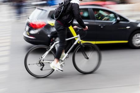 cyclist in city traffic in motion blur