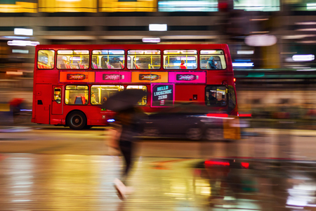 busses: London, UK - June 19, 2016: red double decker bus in motion blur in London night traffic. The famous red busses are one of the main iconic symbols of London. Editorial