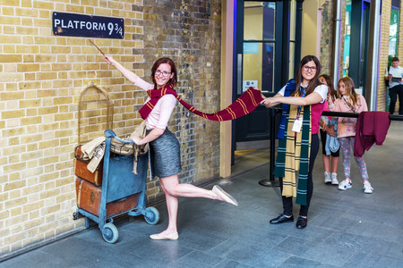 alfarero: Londres, Reino Unido - 16 de junio 2016: 9 Plataforma de tres cuartos en la estación de Kings Cross con personas no identificadas. La plataforma es un ser ficticio de las películas de Harry Potter, instalado en Kings Cross para los turistas
