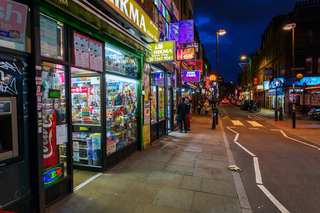 poorer: London, UK - June 16, 2016: Brick Lane in the London district Shoreditch at night. Shoreditch is a inner city district of London. It was one of the poorer districts but today very trendy.