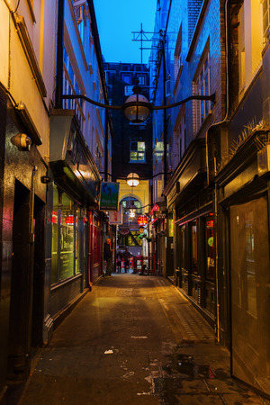 London, UK - June 18, 2016: dark alley in Chinatown of London at night. Chinatown is part of the Soho area with a range of Chinese restaurants and other Chinese run businesses.