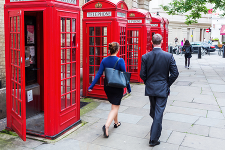 passerby: London, UK - June 16, 2016: unidentified passerby at Covent Garden with traditional red phone boxes. the red phone boxes are iconic symbols of London