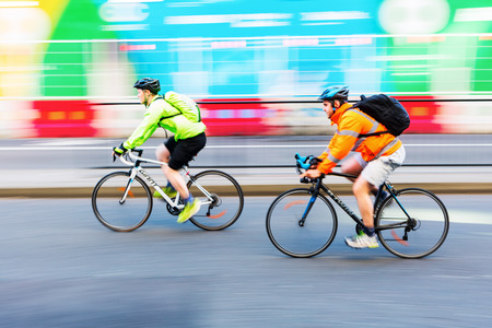 increasingly: London, UK - June 20, 2016: unidentified cyclists in motion blur in the city traffic of London. Cycling is an increasingly popular way to get around London.