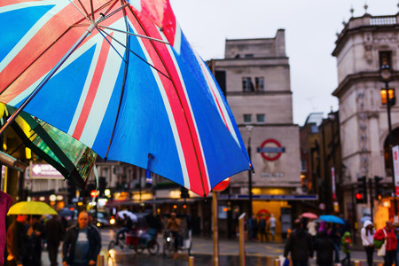 lloviendo: umbrella with union flag in front of a square in the blurred background in London, UK, at a rainy evening Foto de archivo
