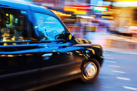 London Taxi in night traffic with abstract motion blur Standard-Bild