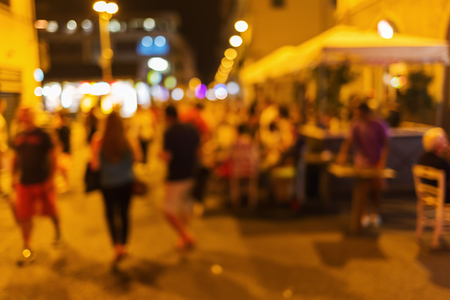 out of town: out of focus picture of a night scene with people and street restaurants in the old town of Florence, Italy