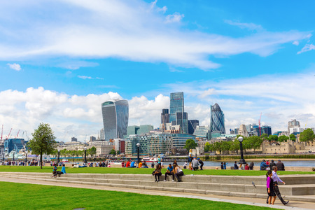 southwark: London, UK - June 15, 2016: London cityscape seen from the Thames promenade at Southwark with unidentified people. London is one of the most important cultural, finance and trade cities of the world