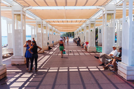 approximately: Nice, France - July 25, 2016: Promenade des Anglais with unidentified people. It is a promenade along the Mediterranean at Nice, extending a distance of approximately 7 km