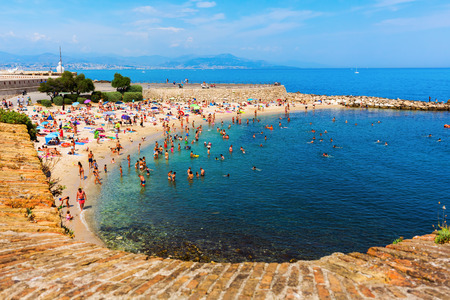 azur: Antibes, France - July 24, 2016: city beach of Antibes with unidentified people. Antibes is a Mediterranean resort in the Alpes-Maritimes department of southeastern France, on the Cote d Azur