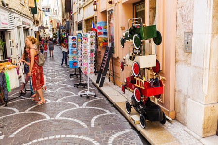 azur: Antibes, France - July 24, 2016: alley in the old town of Antibes with unidentified people. Antibes is a Mediterranean resort in the Alpes-Maritimes department of southeastern France, on Cote d Azur