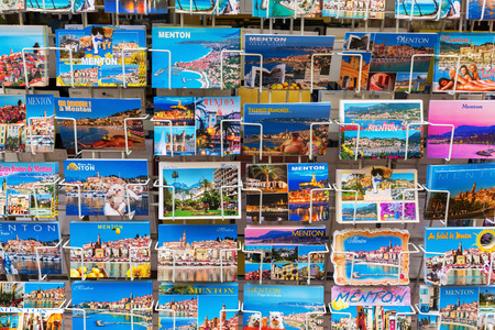menton: Menton, France - July 30, 2016: postcards at a souvenir shop in Menton. Menton is a popular seaside resort at the French Riviera, near the Italian border