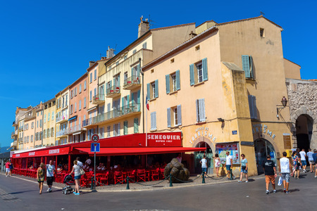 jetset: Saint Tropez, France - August 03, 2016: buildings in the harbor of St Tropez with unidentified people. St Tropez is a seaside resort at the Cote dAzur and popular for the European and American jet set