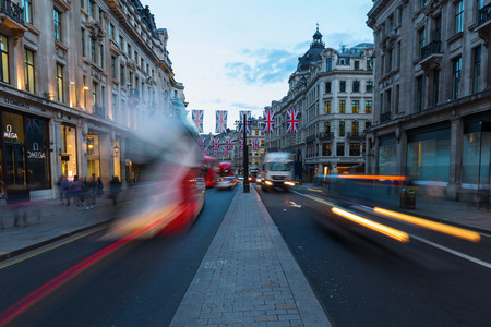 west end: London, UK - June 16, 2016: traffic on Regent Street at dusk, with unidentified people. Regent Street is one of the major shopping streets in the West End of London.