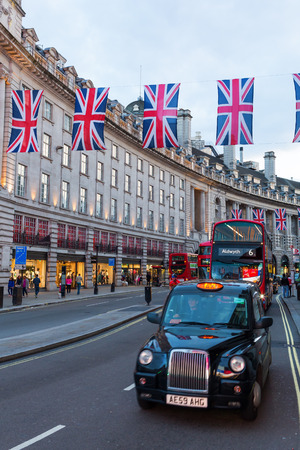 regent: London, UK - June 16, 2016: traffic on Regent Street at dusk, with unidentified people. Regent Street is one of the major shopping streets in the West End of London.
