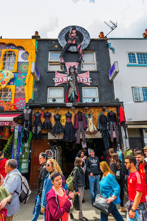 strongly: London, UK - June 17, 2016: unique shopping street in Camden with unidentified people. The area hosts street markets and music venues which are strongly associated with alternative culture