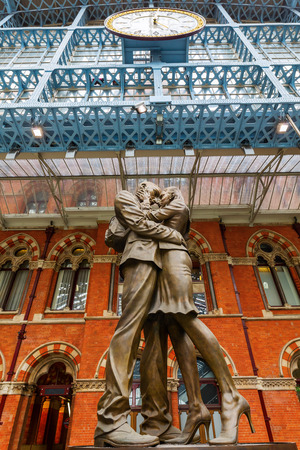 pancras: London, UK - June 16, 2016: statue -The Meeting Place- at St. Pancras Station in London. Its a 9m tall bronze statue of an intimate pose by the world renowned sculptor Paul Day. Editorial