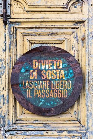 no parking sign: decayed no parking sign on a house door of an Italian town Stock Photo