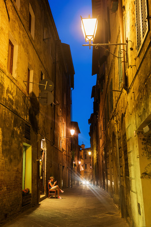 Siena, Italy - July 07, 2016: night scene with unidentified people in Siena. Siena is one of the nations most visited tourist attractions, the old town is declared as UNESCO world heritage site Editorial
