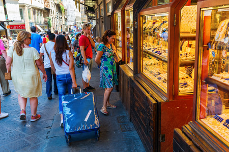 Florence, Italy - July 04, 2016: Ponte Vecchio with unidentified people. It is a Medieval arch bridge over the Arno River, with shops built along it, today jewelers, art dealers and souvenir sellers