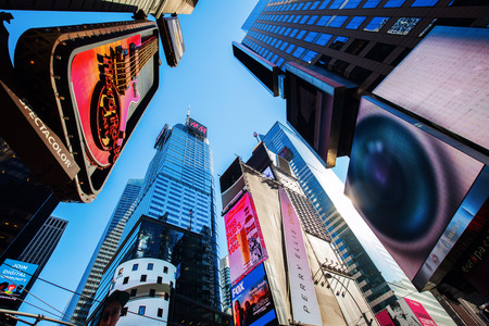 New York City, USA - October 06, 2015: Low angle view of the skyscrapers at Times Square, NYC. It is one of the worlds busiest pedestrian intersections and a major center of worlds entertainment industry Editorial