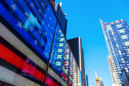 broadway tower: New York City, USA - October 06, 2015: US flag neon sign at Times Square, Manhattan. Times Square one of the worlds busiest pedestrian intersections and a major center of worlds entertainment industry