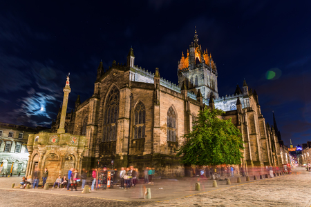 giles: Edinburgh, Scotland - September 10, 2016: St. Giles Cathedral with unidentified people at night. Its distinctive crown steeple is a prominent feature of the city skyline