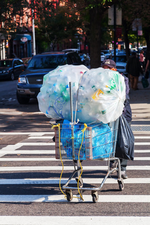 empties: New York City, USA - October 9.2015: homeless man pushing a shopping cart with empties over the street. Homelessness is a social trouble in NYC. Every year about 100,000 people loosing Their shelter.