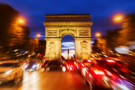 champs elysees: picture with camera made zoom effect of the famous Triumphal Arch in Paris, France, at night