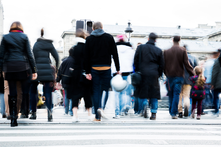 picture with motion blur of a crowd of people crossing a city street at the pedestrian crossing Stock Photo