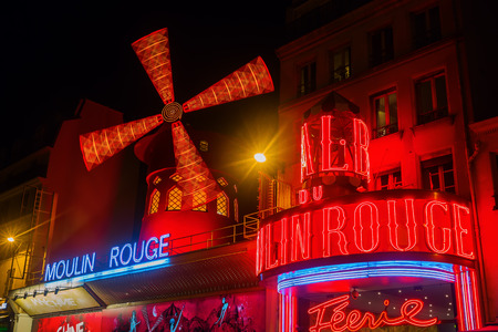 moulin: Paris, France - October 20, 2016: Moulin Rouge at night. It is a world famous cabaret in Paris. Today its a tourist attraction, offering musical dance entertainment for visitors from around the world