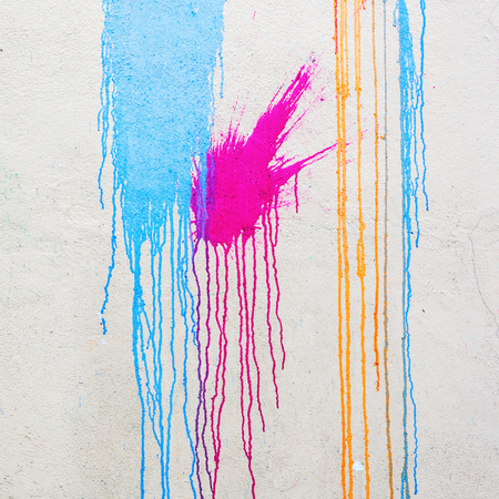 splotches: white wall with colorful stains and flowing paint Stock Photo