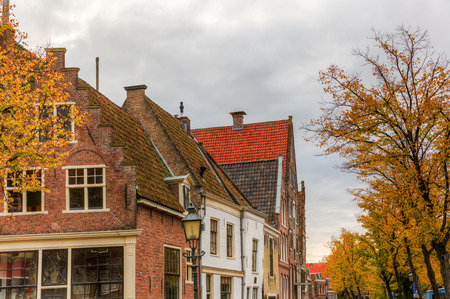 hoorn: historic buildings in the old town of Hoorn, The Netherlands, with autumnal colored trees