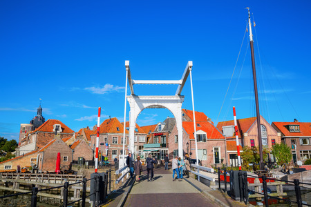 Enkhuizen, Netherlands - October 09, 2016: historical bascule bridge in Enkhuizen with unidentified people. Enkhuizen has today one of the largest marinas in the Netherlands