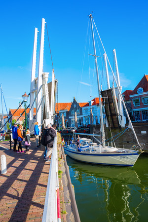 Enkhuizen, Netherlands - October 09, 2016: sailboat under bascule bridge in Enkhuizen with unidentified people. Enkhuizen has today one of the largest marinas in the Netherlands